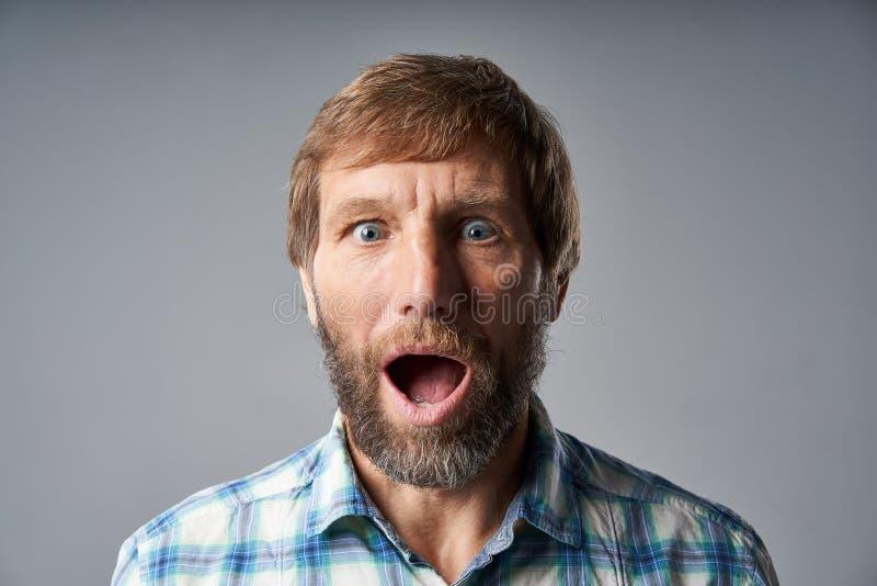 Den förvånade mogna mannen i rutig skjorta med munnen öppnade arkivbilder