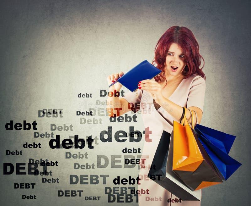 Den förvånade och besvikna unga kvinnan har en tom plånbok som ger ut för mycket pengar på shopping Chockat om enormt skuldbelopp royaltyfri fotografi
