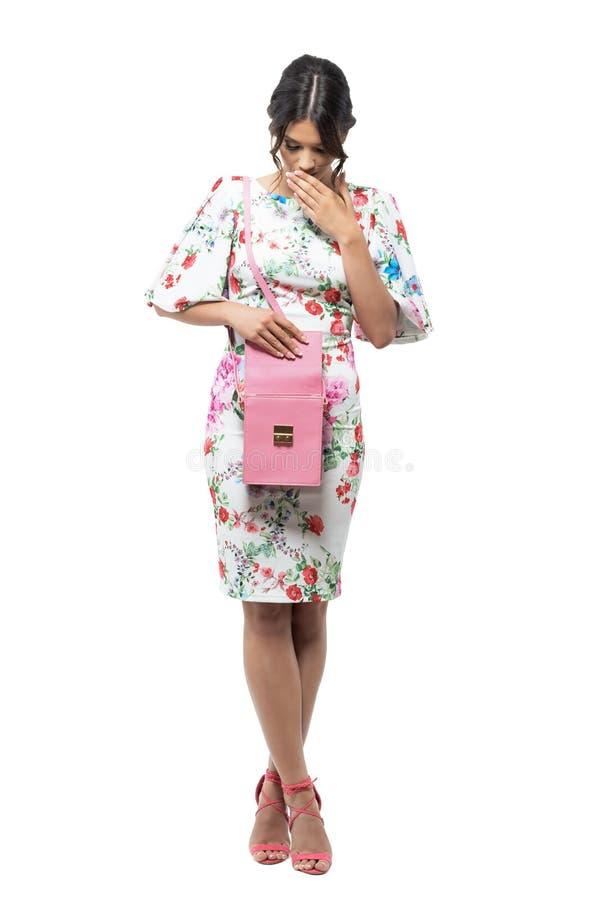 Den förvånade unga eleganta trendiga kvinnan grundar något i hennes rosa handväska arkivfoto