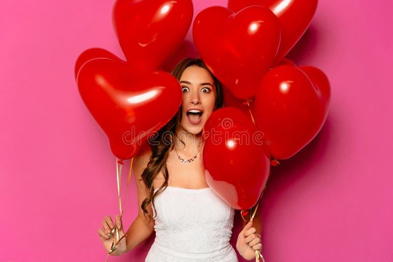 Den förvånade unga kvinnan med hjärta formade luftballonger arkivbild
