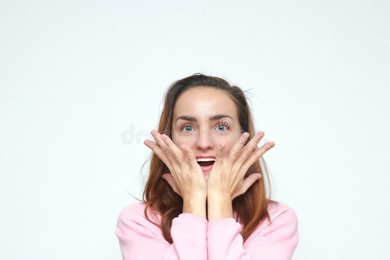 Den förvånade unga kvinnan rätar ut hennes armar till sidan, står på en vit bakgrund se kameran arkivfoto