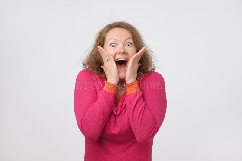 Den förvånade unga kvinnan som ler och rymmer henne, gömma i handflatan nära framsida Hon är chockad med försäljningspriser Är de royaltyfri fotografi