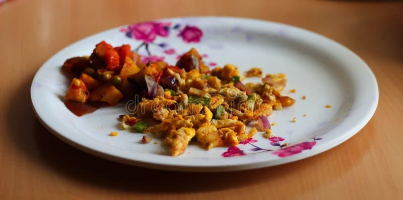Den förvanskade äggomletten och den blandade grönsaken tjänade som på en platta Gjord maträtt för indier hem Slapp fokus royaltyfria foton