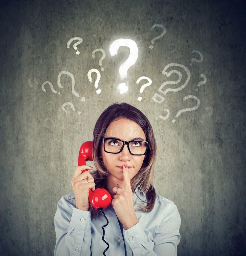 Den förvirrade bekymrade kvinnan som talar på en telefon, har många frågor royaltyfri foto