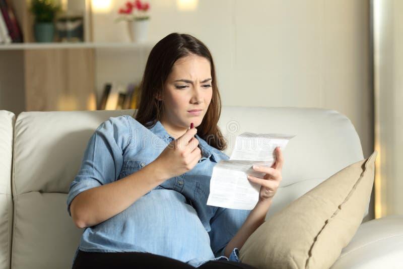 Den förvirrade gravida kvinnan som läser en broschyr för, tar en preventivpiller royaltyfri bild