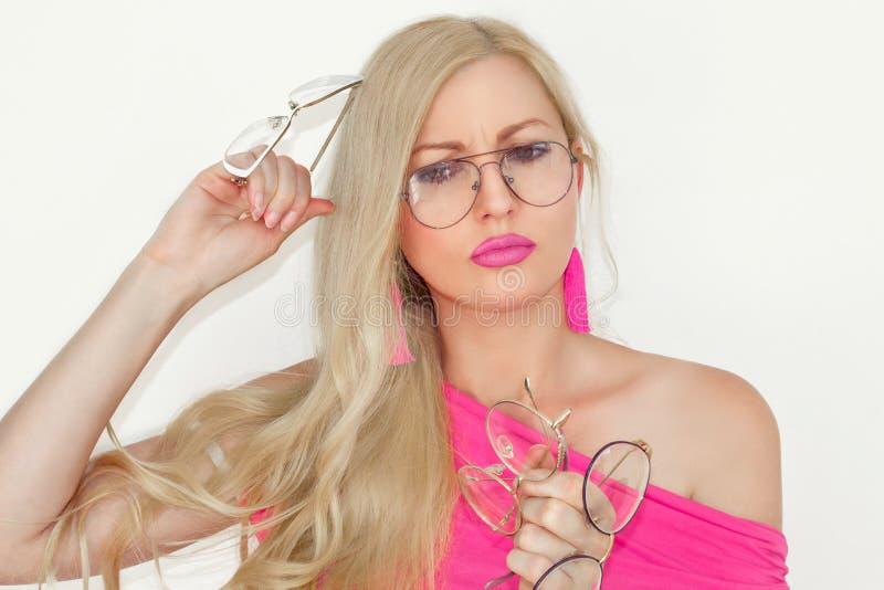 Den förvirrade härliga unga blondinen i exponeringsglas, håll tre par av exponeringsglas i händer och jämför dem Svårt val av exp royaltyfria foton