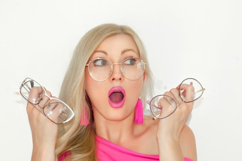 Den förvirrade härliga unga blondinen med exponeringsglas, håll tre par av exponeringsglas i hennes händer och jämför dem med hen arkivfoton