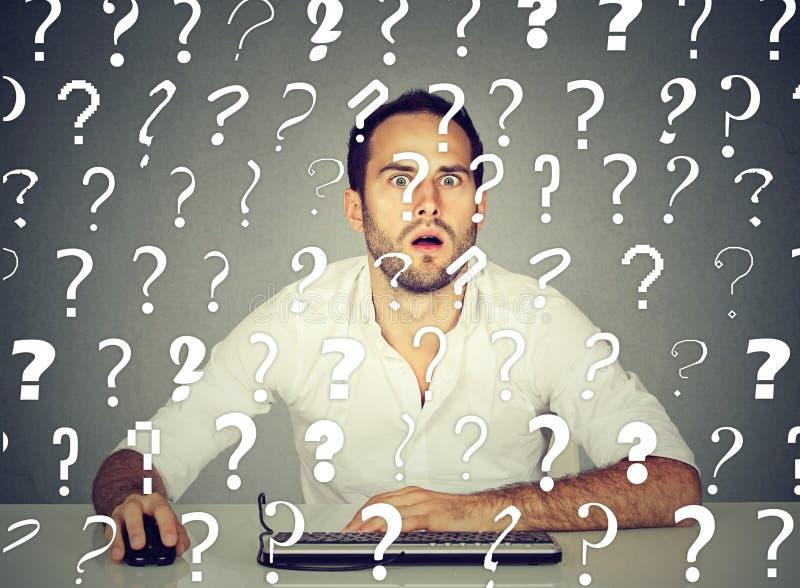Den förvirrade mannen som arbetar på den skrivbords- datoren, har många frågor royaltyfri fotografi