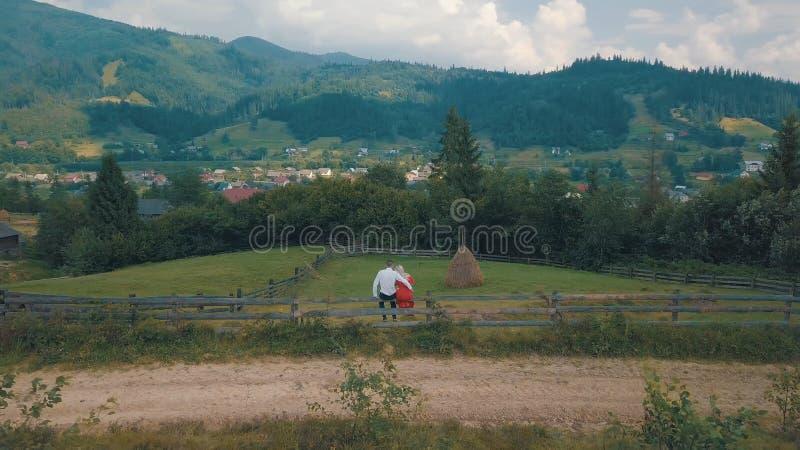 Den f?r?lskade mannen och kvinnan sitter p? staketet n?ra byn i bergen arkivbild