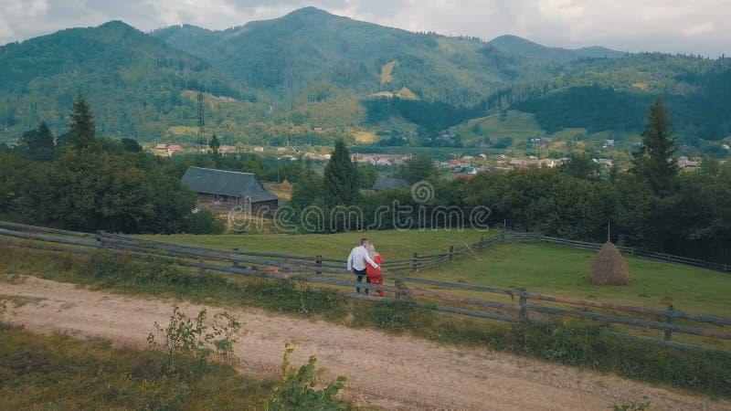 Den f?r?lskade mannen och kvinnan sitter p? staketet n?ra byn i bergen arkivfoto