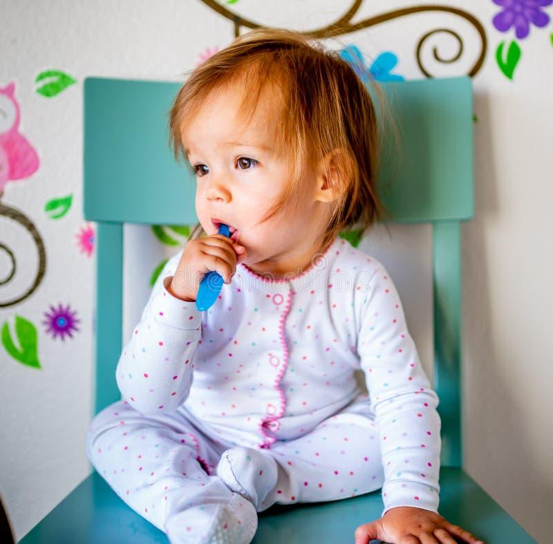 Den f?rtjusande litet barnflickan borstar hennes t?nder i pyjamas bakgrund suddighetdde den skyddande pillen f?r maskeringen f?r  arkivfoto