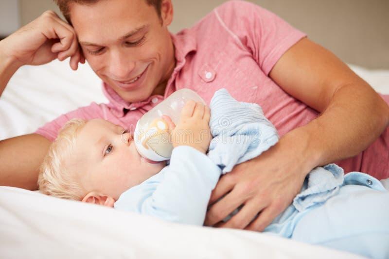 Den faderGiving Baby Son flaskan av mjölkar royaltyfri fotografi