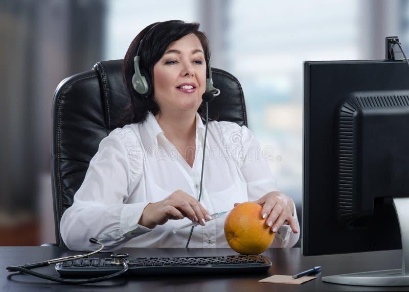 Den faktiska doktorn förklarar teknik för subkutan injektion med grapefrukten arkivfoto
