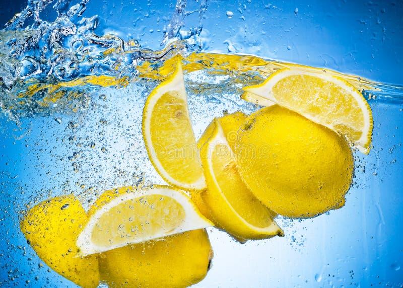 den fallande citronen skivar färgstänk under vatten arkivfoto