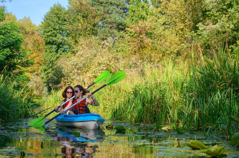 Den familjkayaking, modern och barnet som paddlar i kajak på flodkanoten, turnerar, den aktiva hösthelgen och semestern, sporten  arkivfoto