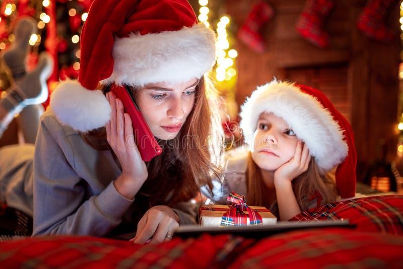 Den familjmodern och dottern i hattar och pyjamas som väljer gåvor på den digital minnestavlan och mamma, kallar Santa Claus vid  arkivbilder