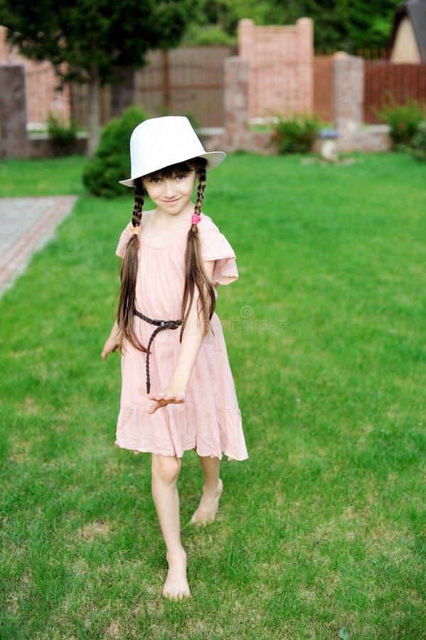 Den fantastiska lilla flickan i rosa färger klär och den vita hatten arkivbild