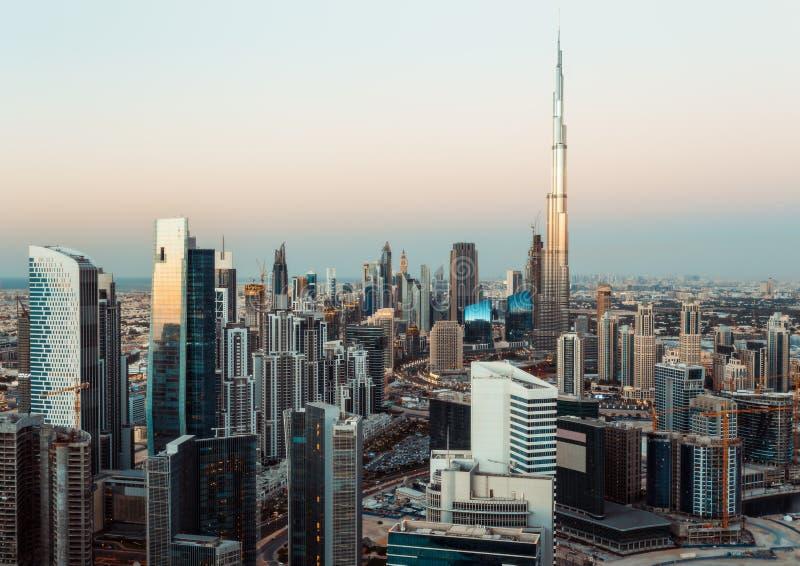 Den fantastiska taksikten av den Dubai affärsfjärden står högt på solnedgången royaltyfri foto