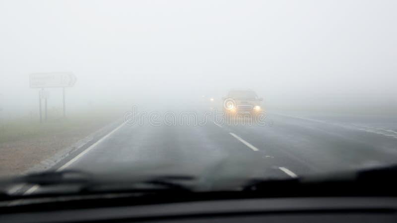 den farliga körande hårda vägen för dimma ser till royaltyfria foton
