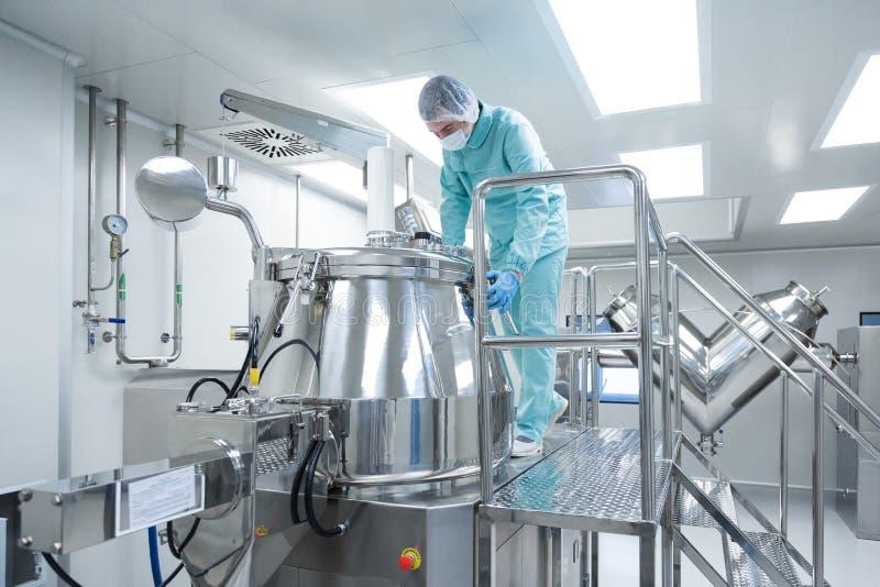 Den farmaceutiska fabriksmanarbetaren i skyddskläder fungerar produktionslinjen i sterila arbetsförhållanden arkivfoton