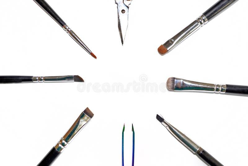 Den fastställda Isolated för hjälpmedelsminkkonstnären uppsättningen av olika borstar för makeupkonstnär och saxen ligger i en ci arkivbilder