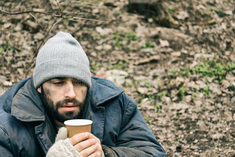 Den fattiga hemlösa mannen med koppen parkerar in royaltyfria foton