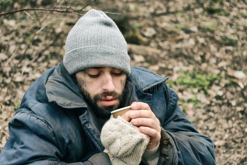 Den fattiga hemlösa mannen med koppen parkerar in royaltyfri fotografi