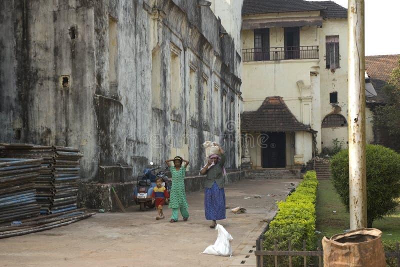 Den fattiga kvinnan bär en tung påse på hennes huvud och bredvid henne är hennes dotter och son Indien Goa - 29 Januari 2009 royaltyfria bilder