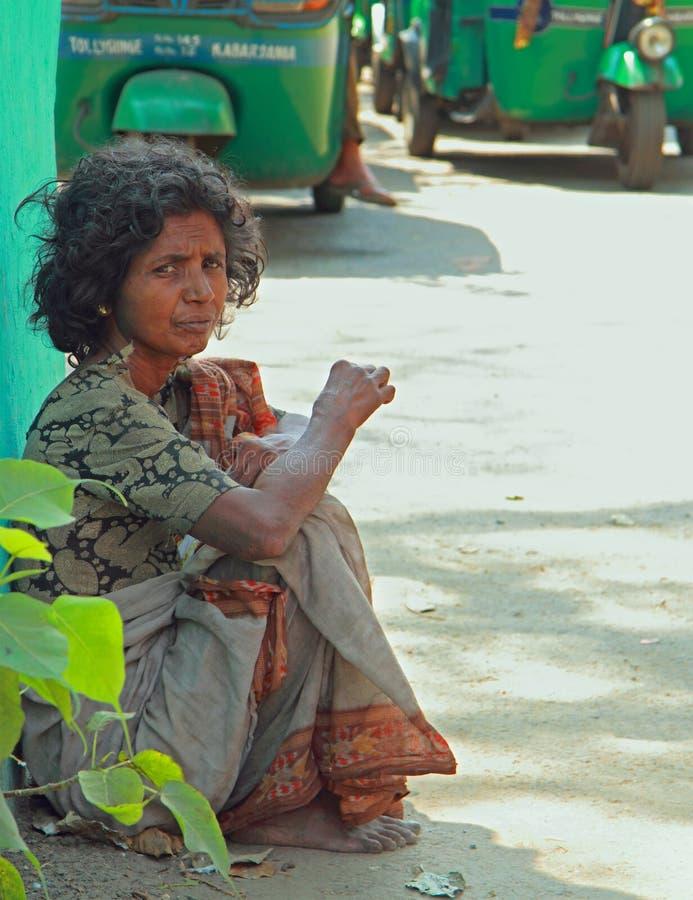 Den fattiga kvinnan sitter på trottoaren i Kolkata arkivfoto