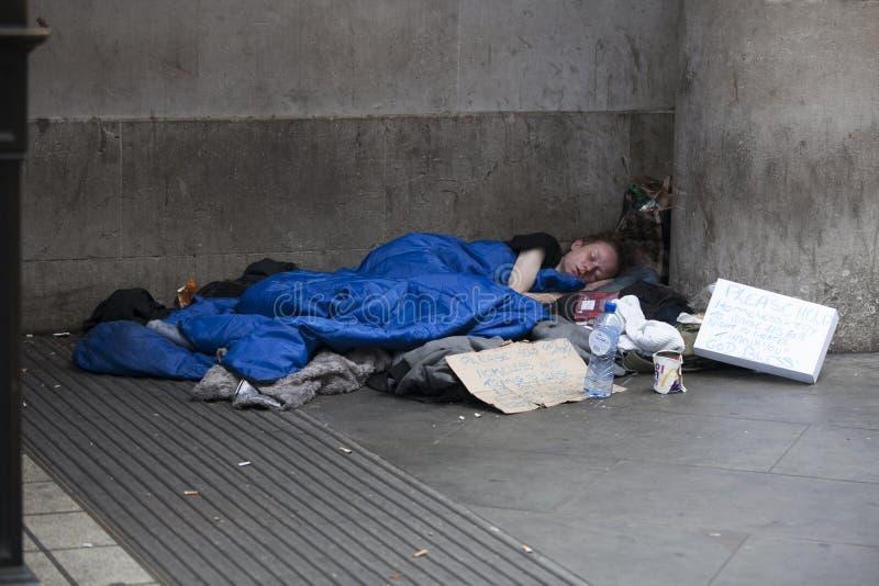 Den fattiga tiggarekvinnan halkar på trottoaren arkivfoton
