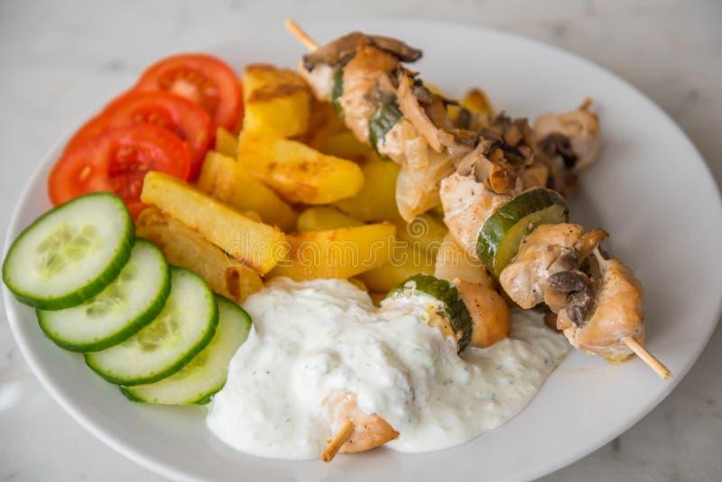 Den fega kebaben tjänade som med den amerikansk potatos, gurkan, tomater och tzatziki royaltyfria bilder