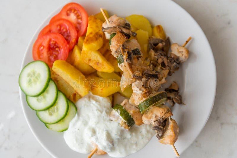 Den fega kebaben tjänade som med den amerikansk potatos, gurkan, tomater och tzatziki royaltyfri fotografi