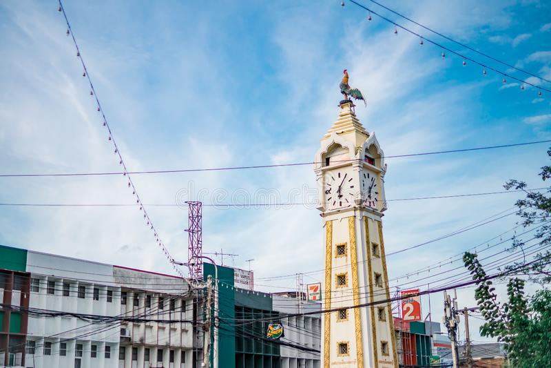 Den fega statyn på gult klockatorn med en smutsig elektricitetstråd mot blå himmel in royaltyfria foton