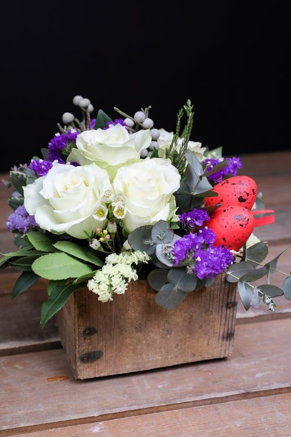 Den festliga blommaordningen av vita rosor, vit- och blåttkermek och andra växter, röda ägg för påsk dekorerade på royaltyfri bild