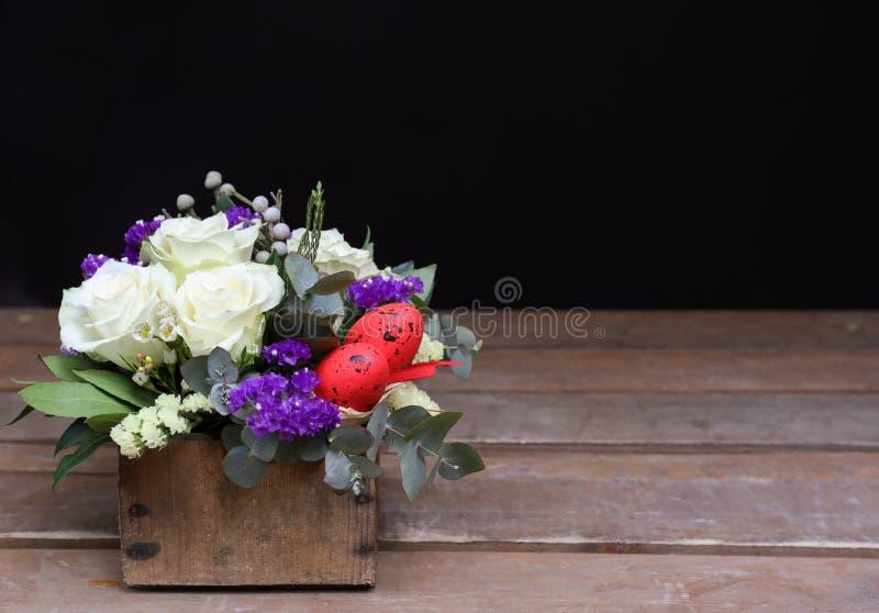 Den festliga blommaordningen av vita rosor, vit- och blåttkermek och andra växter, röda ägg för påsk dekorerade på arkivfoton