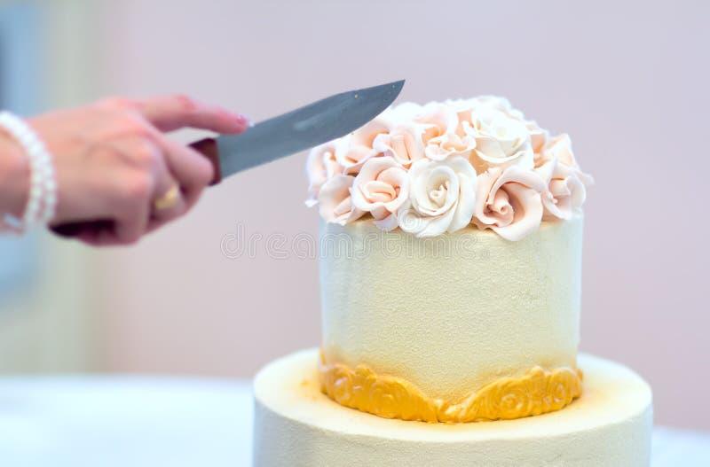 Den festliga bröllopstårtan med blommor, guling-apelsinen blommor, britsen, härligt som är försiktig, bruden, klipper kakan arkivfoto