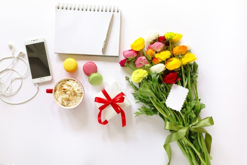 Den festliga morgonbegreppssmörblomman blommar buketten, gåvaasken, kopp av cappuccino, makarons bakar ihop, mobilen, den rena an arkivfoto
