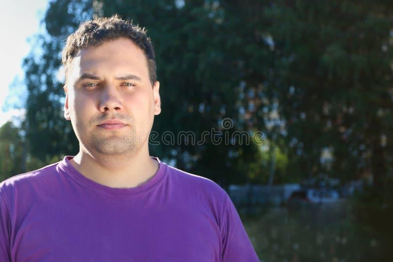 Den feta allvarliga mannen i t-skjorta poserar utomhus- i solljus royaltyfria bilder