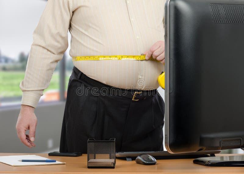 Den feta chefen beräknar avstånd runt om hans midja royaltyfri fotografi