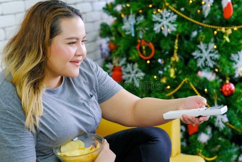 Den feta flickan äter potatischiper och hållande ögonen på TV i hennes hus under jultid med begreppsavkoppling hemma under arkivfoton