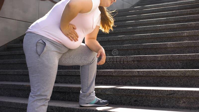 Den feta flickan känner knipet i mage, överviktorsakshälsoproblem som är tillbaka smärtar royaltyfri fotografi