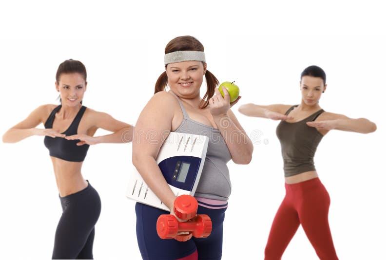 Den feta kvinnan bantar på göra konditionövning arkivbild
