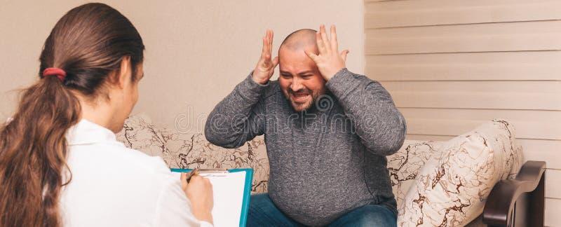 Den feta mannen i spänning berättar känslomässigt om hans fördjupning och problem Konsultera för psykolog arkivfoton