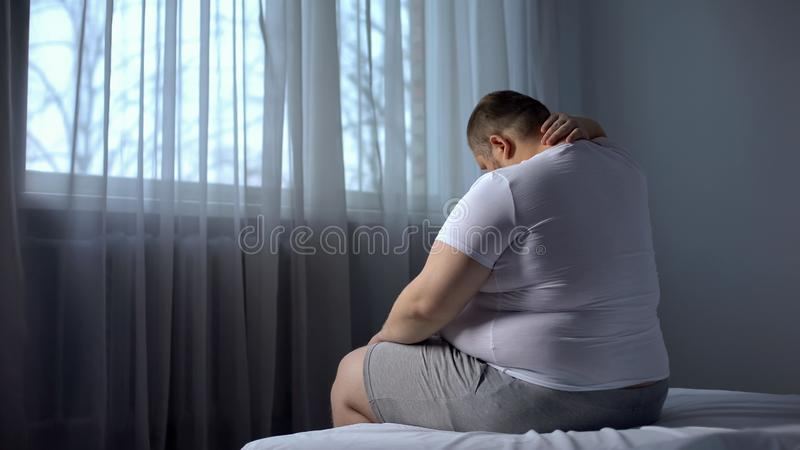 Den feta mannen som masserar halsen, baksida smärtar problemet, fysisk aktivitet för brist, rheumatology arkivfoton