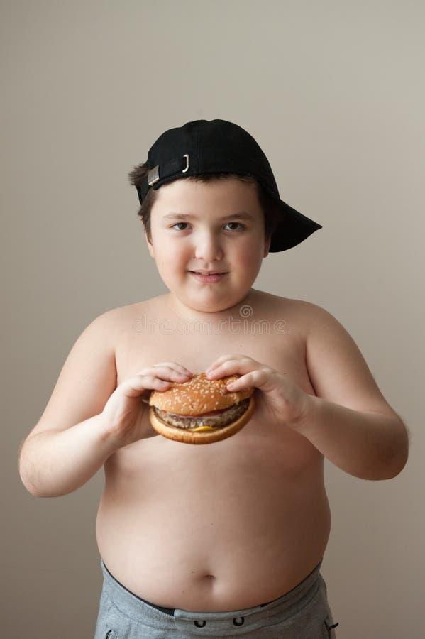 Den feta pojkehamburgaren äter matövervikt bantar näring royaltyfri bild