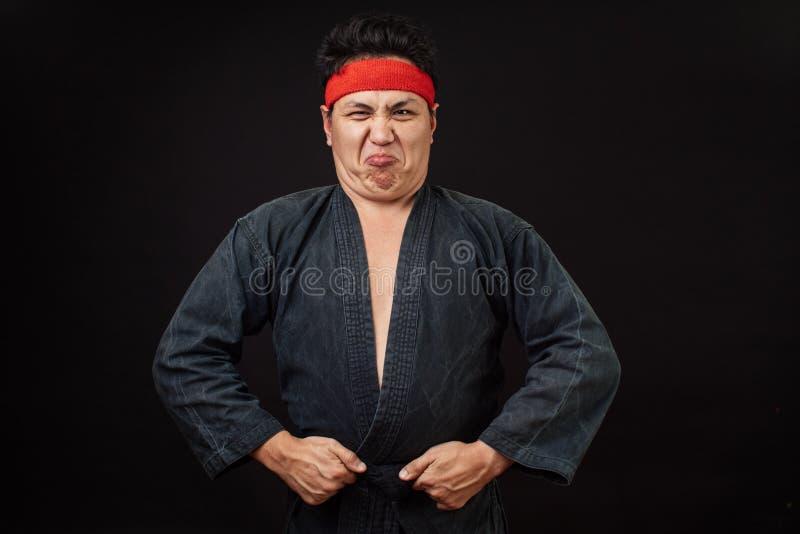 Den feta stramade åt mannen visar hans muskel royaltyfri bild