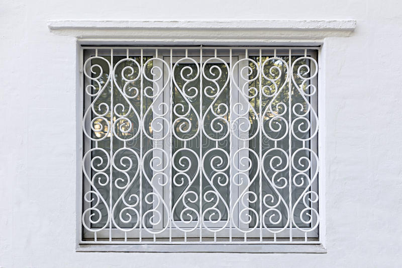 Den figurerade ramen av fönstret med järn förfalskade det vita gallret royaltyfri bild