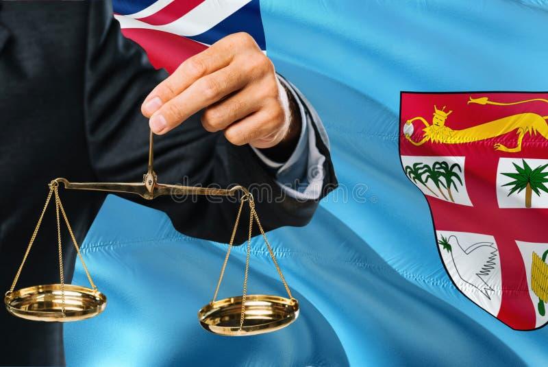 Den Fijian domaren rymmer guld- våg av rättvisa med fijiansk vinkande flaggabakgrund Jämställdhettema och lagligt begrepp fotografering för bildbyråer