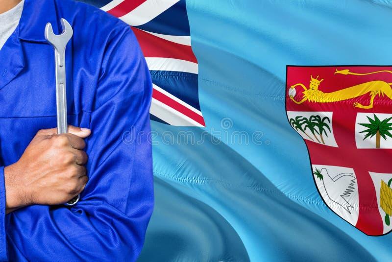 Den Fijian mekanikern i blå likformig rymmer skiftnyckeln mot att vinka fijiansk flaggabakgrund Korsad armtekniker royaltyfri foto