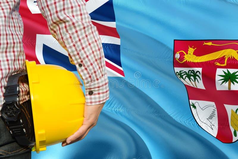 Den Fijian teknikern rymmer den gula säkerhetshjälmen med att vinka fijiansk flaggabakgrund Konstruktions- och byggnadsbegrepp royaltyfria bilder